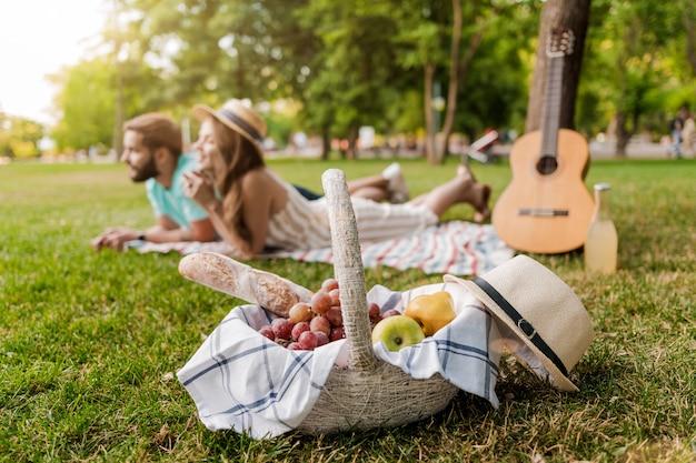 フォーカスで、ピクニックバスケット、ギターでリラックスした公園の芝生の上の若いカップル Premium写真