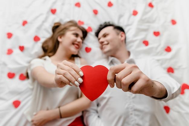 ハートの形をしたベッドで愛の男女 Premium写真