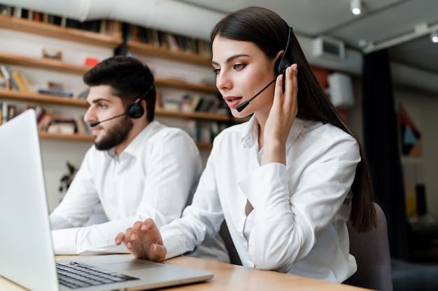 Красивая женщина работает в колл-центр с гарнитурой, отвечая на телефонные звонки клиента Premium Фотографии