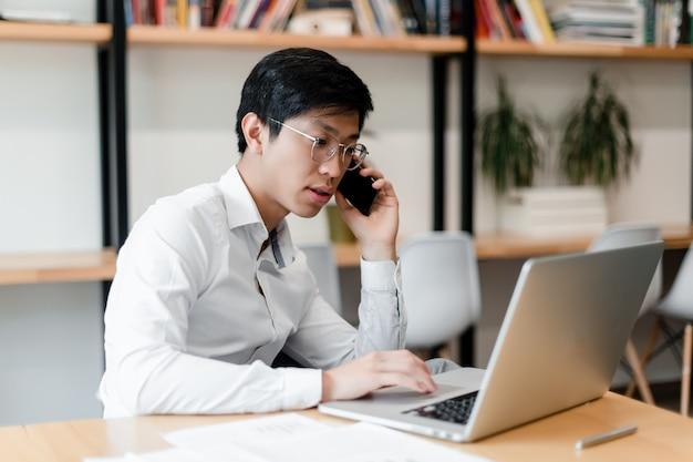 オフィスでアジア系のビジネスマンはラップトップで動作します Premium写真