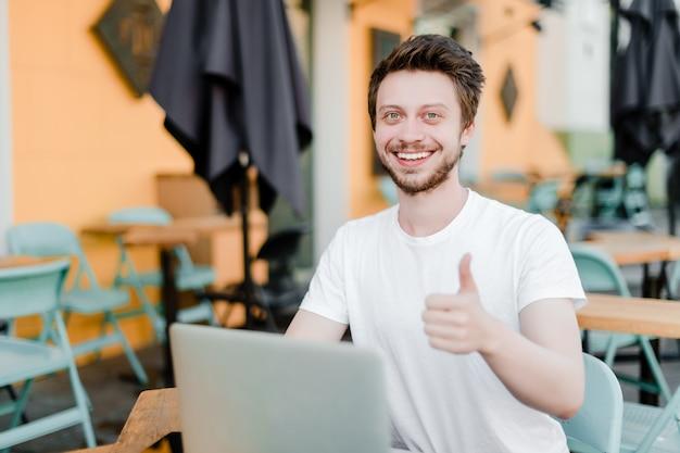 笑みを浮かべて男はラップトップで作業中に親指を表示 Premium写真