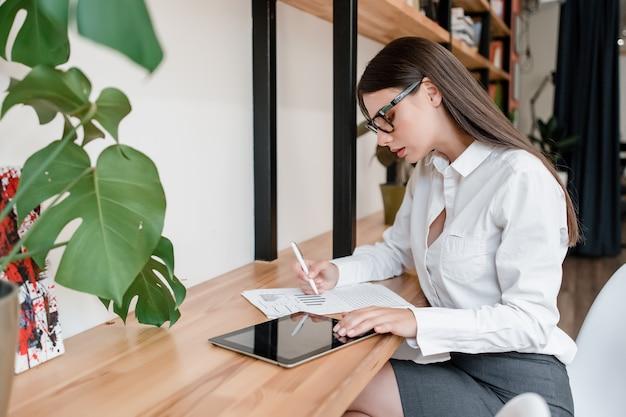 オフィスでタブレットから情報を書くメガネの女性 Premium写真