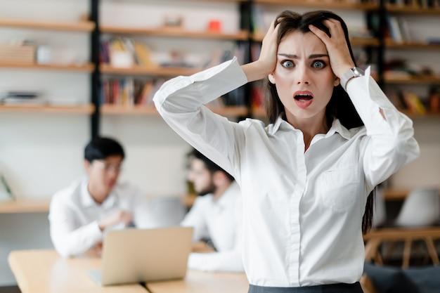 オフィスでショックを受けた女性 Premium写真