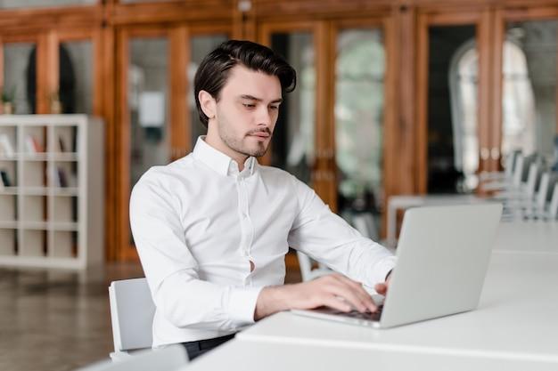 オフィスでラップトップで彼の職場で男 Premium写真