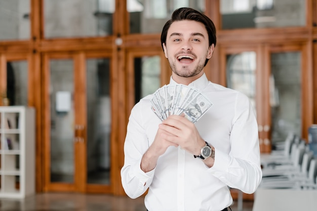 オフィスでお金でハンサムな実業家 Premium写真