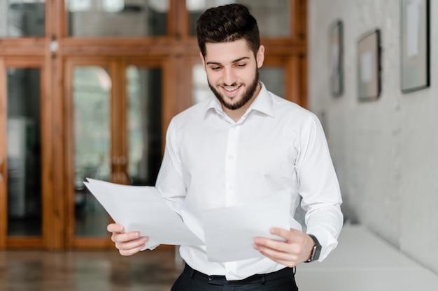 オフィスで論文を持つオフィスワーカー Premium写真