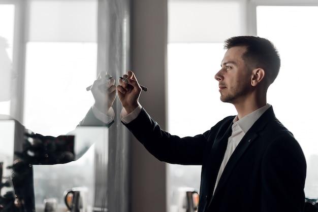 ガラスの壁にグラフを描くオフィスのビジネスマン Premium写真