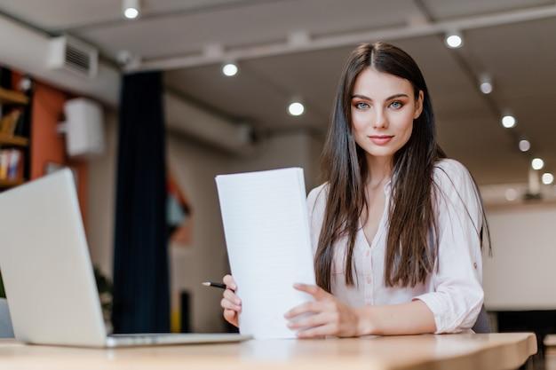 Красивая женщина работает с бумагами и ноутбук в офисе Premium Фотографии