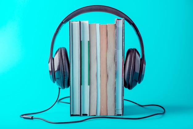 青色の背景に書籍のスタックを持つ黒いヘッドフォン。 Premium写真