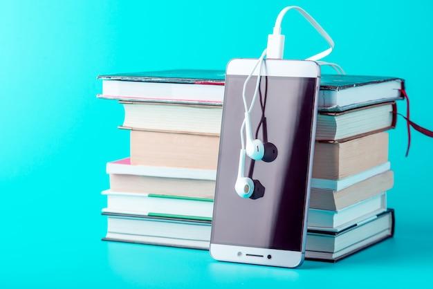 青色の背景に書籍のスタックの横にある白いイヤホンで電話をかけます。 Premium写真