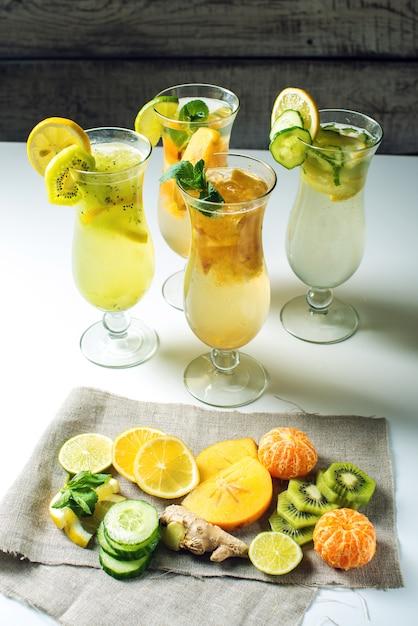 トロピカルフルーツとガラスのハリケーンで氷とレモネードを設定します。 Premium写真