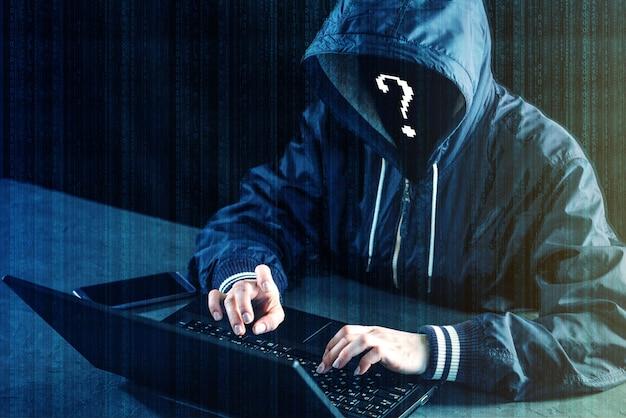 匿名のハッカープログラマーはラップトップを使用してシステムをハッキングします。個人データを盗む。悪意のあるウイルスの感染 Premium写真