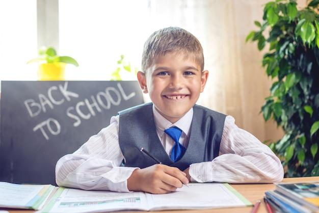 Обратно в школу. милый ребенок, сидя за столом в классе. Premium Фотографии