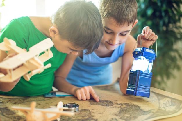 手に飛行機を持った子供たちは、下の地図を探索して新しい冒険に旅立ちましょう。 Premium写真