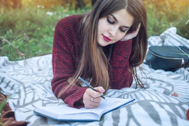 彼女のノートにペンの秋の物語を書いている美しい女性作家。 Premium写真