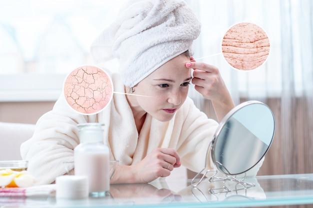 乾燥肌をひび割れと最初のしわで見ている女性。丸は拡大鏡のように肌を大きくする Premium写真