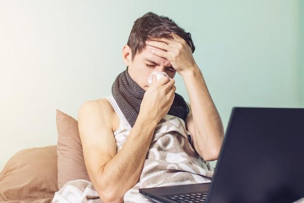 若い男がベッドで横になっている風邪で病気 Premium写真