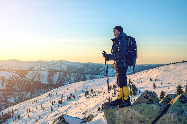 Человек туристов, стоя на снежной вершине на закате Premium Фотографии