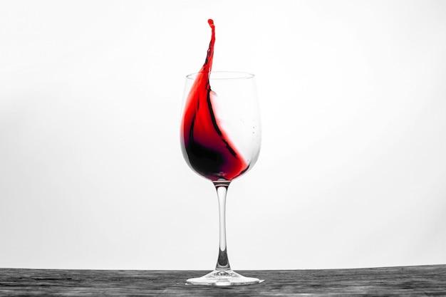 Красное вино в бокале брызгает в движении Premium Фотографии