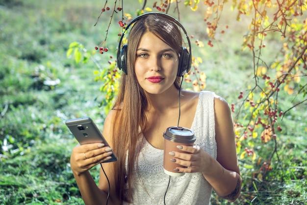 晴れた日にヘッドフォンを身に着けているあなたの電話で音楽を聴く女性。 Premium写真