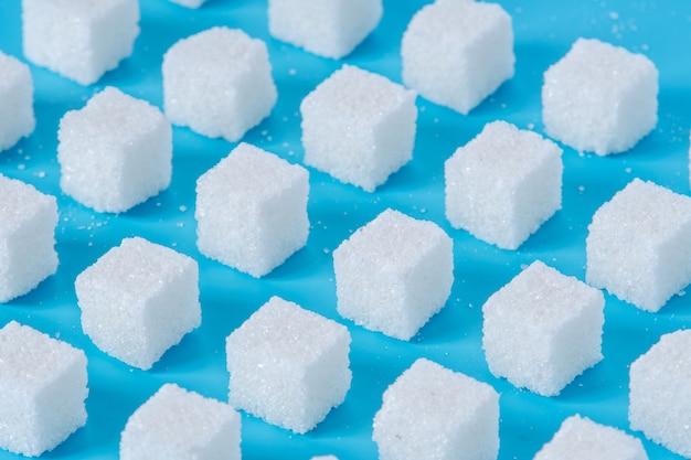 青色の背景に影と砂糖の洗練されたキューブのパターン Premium写真