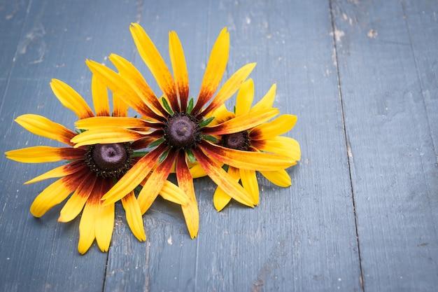 暗い木製のテーブルの上の美しい庭の花 Premium写真