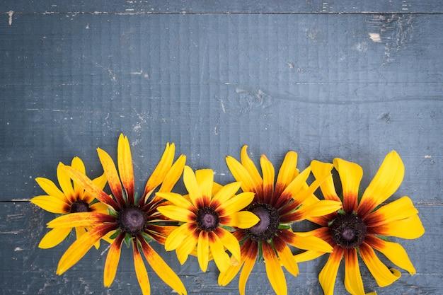 青い木製のテーブルの上の庭の花のフレーム Premium写真