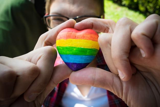 女性の手が虹の縞模様の装飾的な心を保持しています。 Premium写真