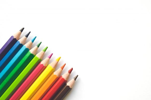 Ряды карандашей цвета на предпосылке белой бумаги, космосе экземпляра. канцелярские товары, снова в школу. Premium Фотографии