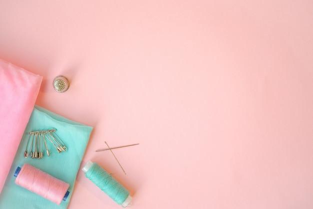ミシンアクセサリー、ピンクの背景にターコイズブルーとピンクの生地。生地、ピン、糸、針。 Premium写真