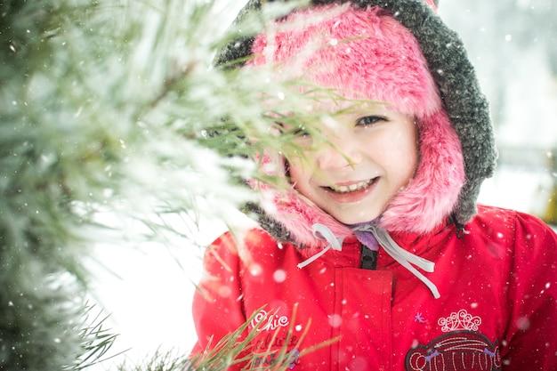 公園の松の枝の近くの小さな女の子 Premium写真