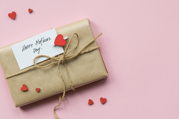 Подарок, завернутый в коричневую крафт-бумагу и галстук-пеньку. подарочная коробка с поздравлением на день матери. вид сверху. Premium Фотографии