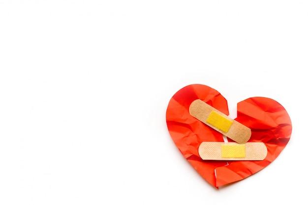 Сломанный красный символ сердца с медицинской патч на белом фоне, концепция любви. исцеление Premium Фотографии