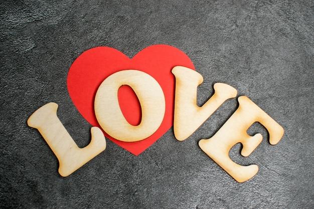 День святого валентина карты фон, красное милое сердце из бумаги с декоративной деревянной слово на темном фоне. день святого валентина романтичный. любовь Premium Фотографии