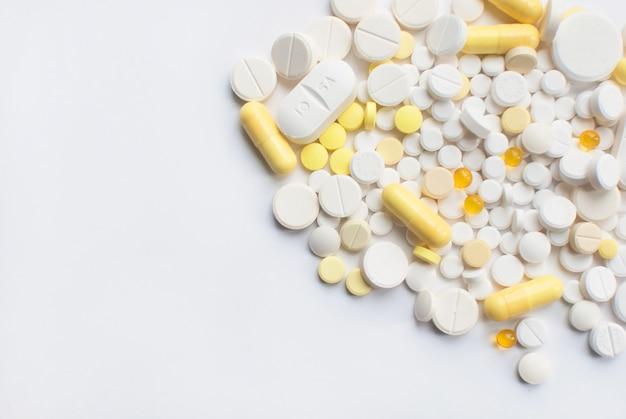 Букет из желтых и белых таблеток и пилюль, изолированных на белом фоне крупным планом. Premium Фотографии
