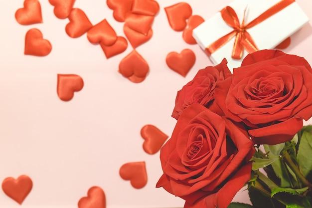 День святого валентина фон, красная роза с красными сердцами и подарочной коробке на розовом фоне, для карты и свадьбы фоне Premium Фотографии