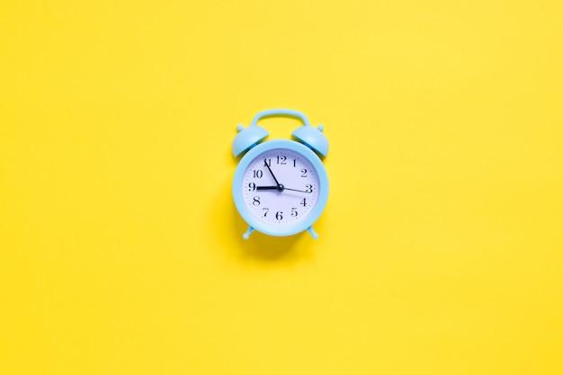 Синий будильник на желтом фоне Premium Фотографии