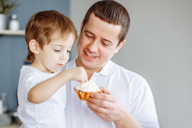 父は台所で彼の幼い息子を供給します。 Premium写真