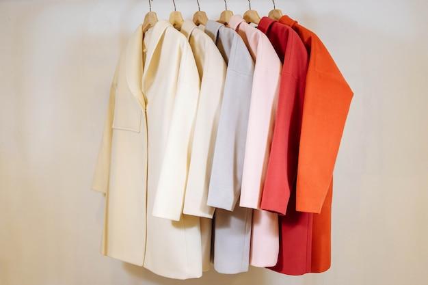 ハンガーに女性のコートの色の行を混在させる Premium写真