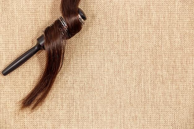ベージュ色の背景の上に黒髪の櫛 Premium写真