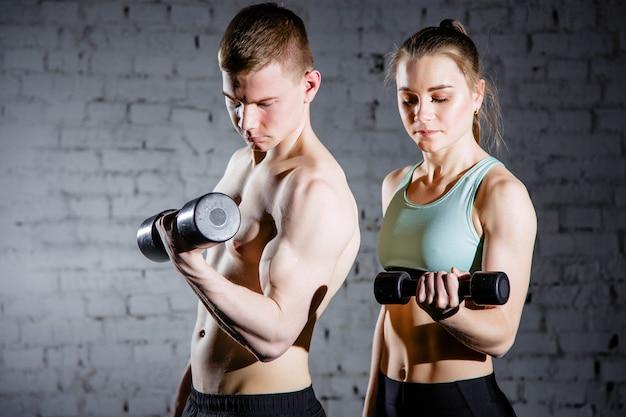 ウエイトトレーニング機器を備えたフィットネスカップル Premium写真