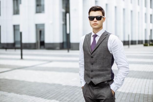 Молодой человек в костюме и солнцезащитные очки на улице в городе Premium Фотографии