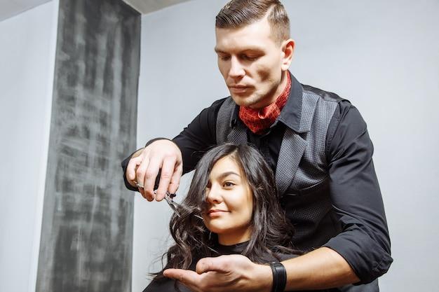 幸せな若い女性と美容院で髪を切るのヒント。 Premium写真