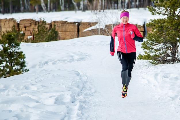 スポーツ女性を実行しています。暖かいスポーティなランニング服を着て寒い冬の森でジョギングする女性ランナー。 Premium写真
