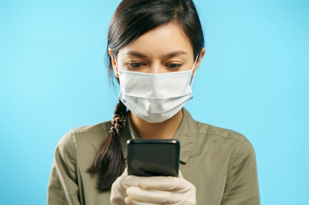 Молодая женщина в защитной медицинской маске и перчатки, используя смартфон на синем фоне. онлайн чат Premium Фотографии
