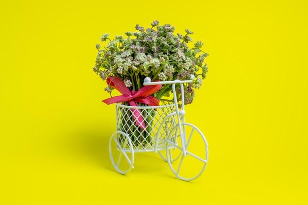 おもちゃの自転車は花を運びます。はがきのアイデア。黄 。ミニマリズム。 Premium写真