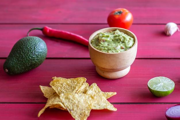 ワカモレとチップナチョス。赤 。メキシコ料理。 Premium写真
