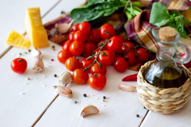 パルメザンチーズ、トマト、オリーブオイル、その他のサラダドレッシングの材料。白色の背景。 Premium写真