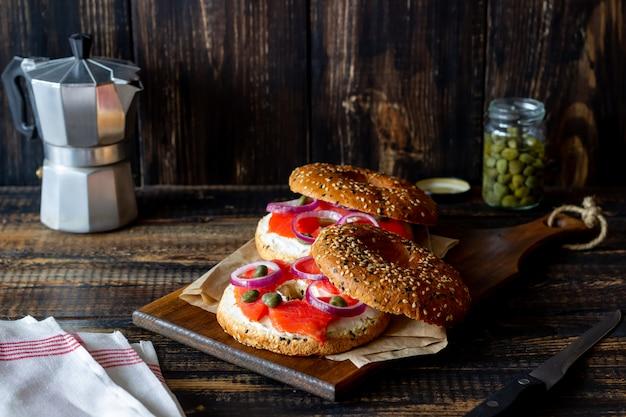 Рогалики с лососем, белым плавленым сыром и каперсами на деревянном фоне. рецепты. здоровое питание. Premium Фотографии