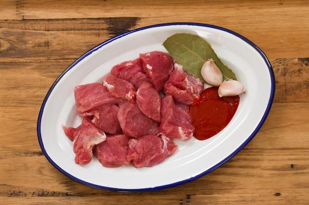 木製の表面に皿にニンニクと生肉 Premium写真